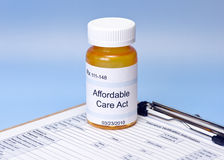 Affordable Care Act Insurance. Affordable Care Act prescription bottle on blue with health iinsurance verification form stock photos