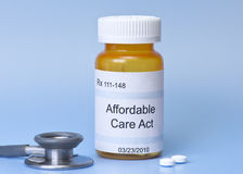 Affordable Care Act. Prescription bottle on blue with sethescope and pills stock photo