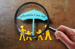 Affordable Care Act search. Paper family under a Affordable Care Act umbrella with magnifying glass royalty free stock photo