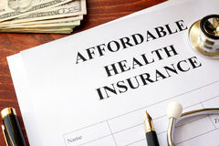 Affordable health insurance. Affordable health insurance policy on a table royalty free stock images