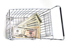 Affordable Shopping. Metal shopping cart with money on white background. American currency stock image