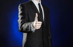 Affär och presentationen av temat: man i svarta gester för en dräktvisninghand på ett mörker - blå bakgrund i den isolerade studi Arkivbild