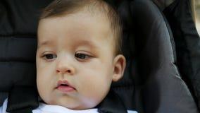 Affronti il neonato abbronzato sei mesi che si siedono in un passeggiatore archivi video