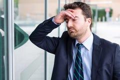 Affronti il ritratto dell'uomo d'affari disperato dopo grande difficoltà sul lavoro Immagine Stock