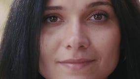 Affronti il ritratto della giovane donna castana esaminando la macchina fotografica e sorridendo sul fondo vago all'aperto stock footage