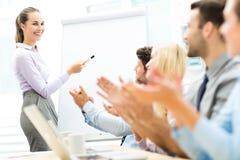 Affärsfolk på en presentation som applåderar Arkivfoton