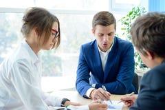 Affärsfolk som analyserar finansiella resultat på grafer runt om tabellen i modernt kontor för begreppsdockor för bakgrund svart  Royaltyfri Bild