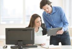 Affärsfolk som diskuterar över den Digital minnestavlan Fotografering för Bildbyråer
