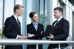 Affärsfolk som framme talar av kontorsbyggnad Arkivfoto