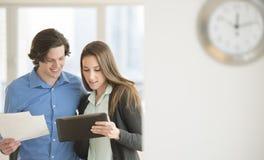 Affärsfolk som i regeringsställning använder den Digital minnestavlan Arkivbild