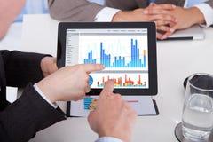 Affärsfolk som i regeringsställning diskuterar grafen på den digitala minnestavlan Arkivbilder