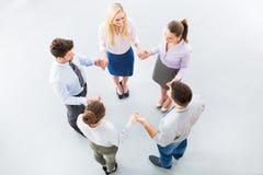 Affärsfolk som rymmer händer för att bilda en cirkel Arkivfoto