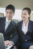 Affärskollegor som använder bärbara datorn i baksäte av bilen Arkivbild