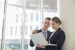 Affärskollegor som i regeringsställning använder bärbara datorn Royaltyfri Bild