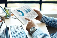 Affärskonsulent som analyserar finansiella diagram som betecknar framsteget i arbetet av företaget Arkivbilder