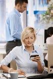 Affärskvinna genom att använda mobil Fotografering för Bildbyråer