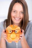 Affärskvinna Holding Piggy Bank med exponeringsglas i regeringsställning Arkivfoton