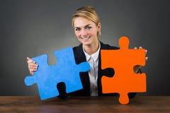 Affärskvinna Holding Puzzle Pieces på skrivbordet Arkivfoto
