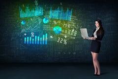 Affärskvinna i regeringsställning med bärbara datorn i hand och tekniskt avancerad graf Arkivbild