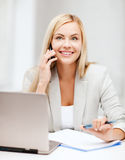 Affärskvinna med bärbara datorn och mobiltelefonen Arkivfoto