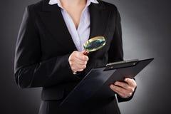 Affärskvinna med förstoringsglaset och skrivplattan Royaltyfri Bild