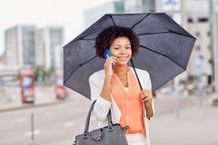 Affärskvinna med paraplyet som kallar på smartphonen Royaltyfri Bild