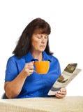 Affärskvinna With Newspaper And som dricker kaffe Royaltyfria Foton