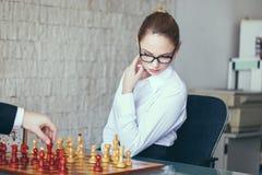 Affärskvinna och affärsman som i regeringsställning spelar schack Arkivfoto