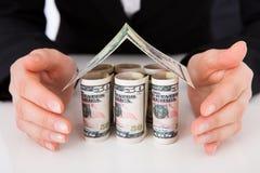 Affärskvinna Protecting House Made av dollarräkningar Royaltyfri Bild