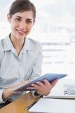 Affärskvinna som använder hennes digitala minnestavla som ler på kameran Arkivfoto