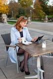 Affärskvinna som använder minnestavlan på lunchavbrott. Arkivbild