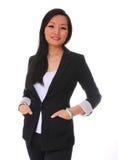 Affärskvinna som ler isolaten. härlig asiatisk kvinna i den svarta affärsdräkten som ser kameran Arkivfoton