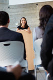 Affärskvinna som levererar presentation på konferensen Arkivbild