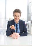Affärskvinna som sätter myntet in i spargrisen Arkivfoto