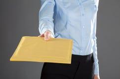 Affärskvinna som ut når bokstaven i gult kuvert Arkivbild