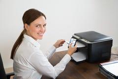 Affärskvinna Using Mobile Phone för utskrift av grafen Royaltyfri Bild