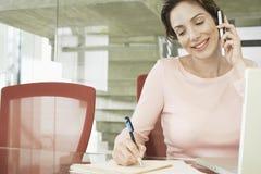 Affärskvinna Using Mobile Phone, medan skriva på notepaden Arkivfoton