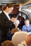 Affärskvinna Using Mobile Phone på den upptagna pendeltåget Royaltyfri Foto