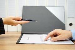 Affärskvinnaerbjudande en penna över ett avtal till klienten Arkivbild