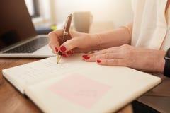 Affärskvinnahandstil i hennes personliga organisatör Fotografering för Bildbyråer
