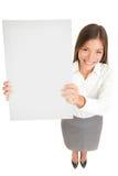 Affärskvinnainnehav upp ett tomt undertecknar Fotografering för Bildbyråer