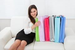 Affärskvinnan With Multicolored Shopping hänger löst sammanträde på soffan Arkivbild