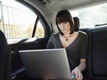 AffärskvinnaUsing Laptop In bil Royaltyfria Bilder