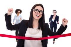 Affärskvinnor som korsar mållinjen som isoleras på vit Arkivbilder