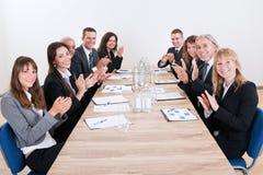 Affärslag som sitter på tabellen och att applådera Arkivbild