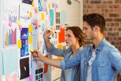 Affärsledare som sätter klibbiga anmärkningar på whiteboard Arkivfoto