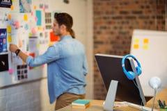Affärsledare som sätter klibbiga anmärkningar på whiteboard Arkivfoton