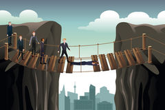 Affärsman Helping His Colleagues som korsar bron för lag Arkivfoton