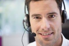 Affärsman i kontoret på telefonen med hörlurar med mikrofon som ser kammen Arkivfoton