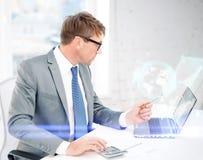 Affärsman med datoren, legitimationshandlingar och räknemaskinen Royaltyfri Bild